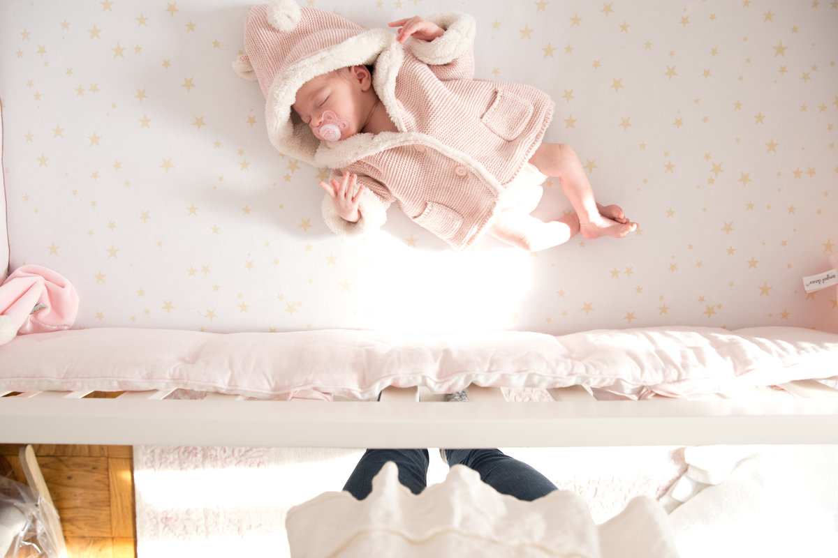 Newborn baby lies in crib as photographer takes a newborn photograph from above