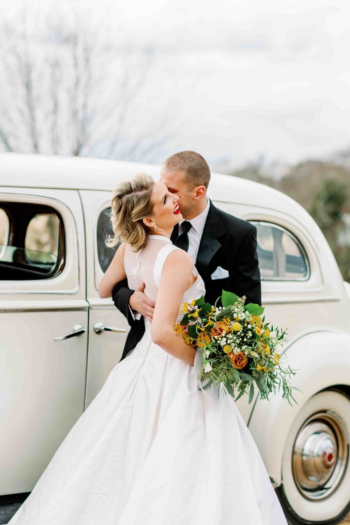 bride and groom embrace in front of mount ida farm