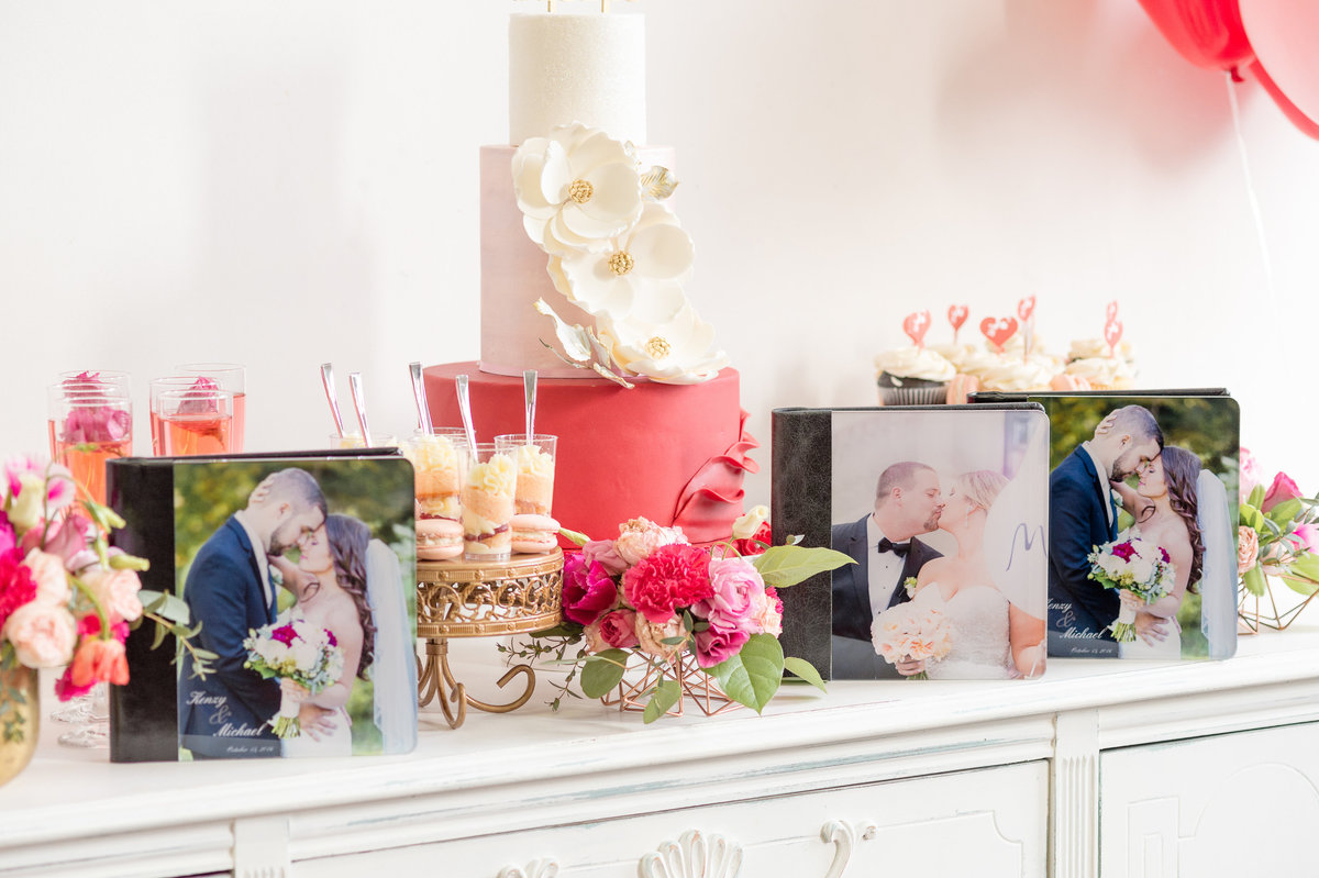 KSS Photography albums sit atop a counter amidst wedding cakes