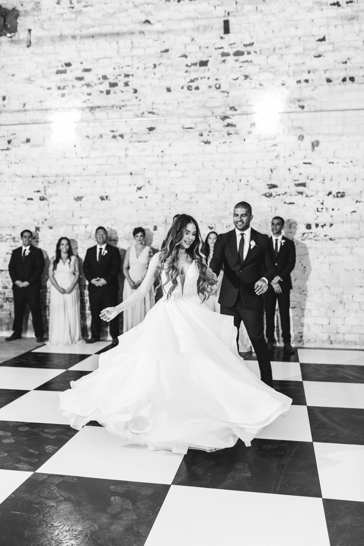 Bride and groom dancing on checkered dance floor smiling together