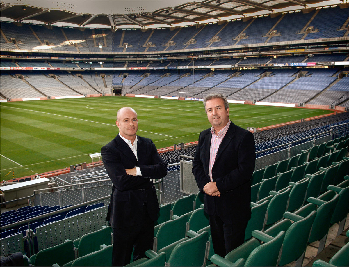 Two businessmen standing in an empty football stadium