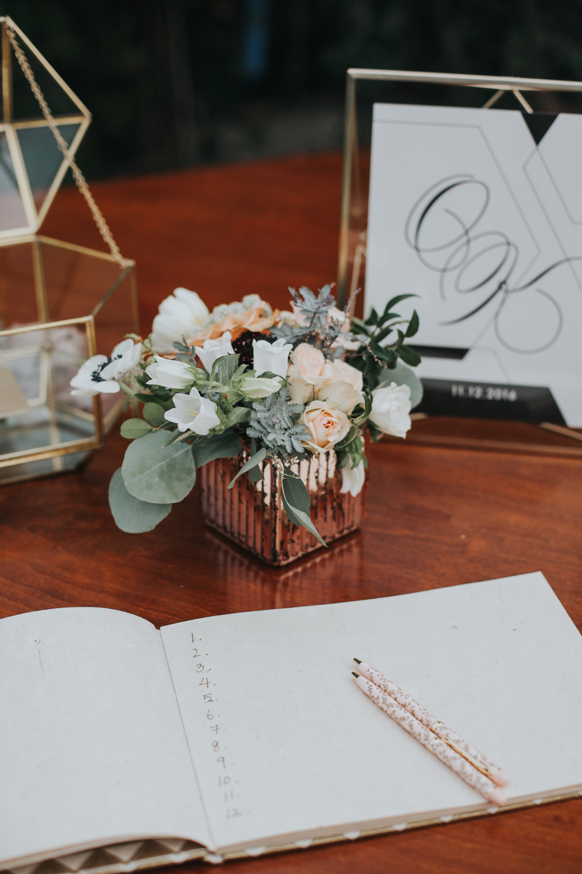 Wedding welcome table guest book and white floral arrangement with eucalyptus leaves