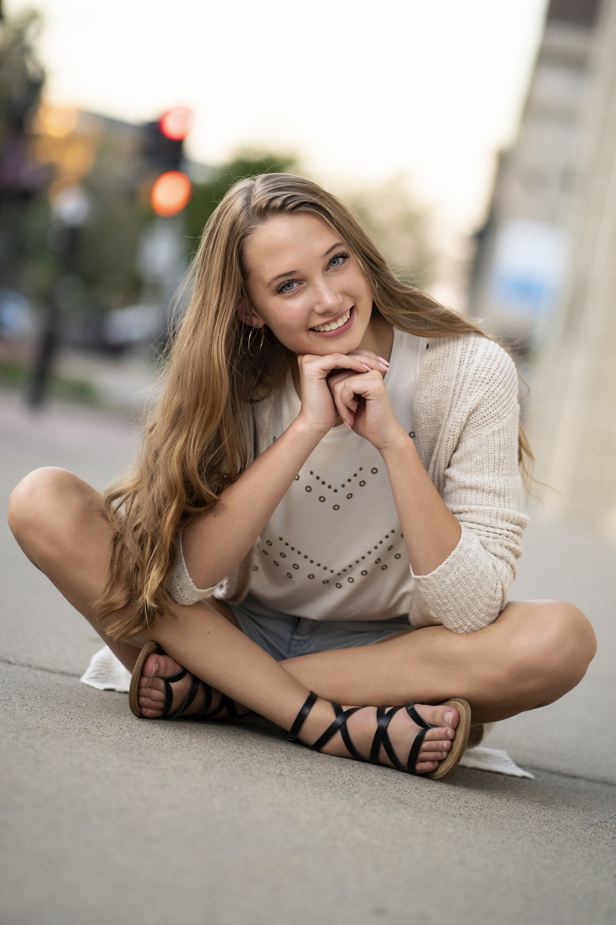 sioux falls south dakota senior photography downtown philips ave girl sitting on sidewalk