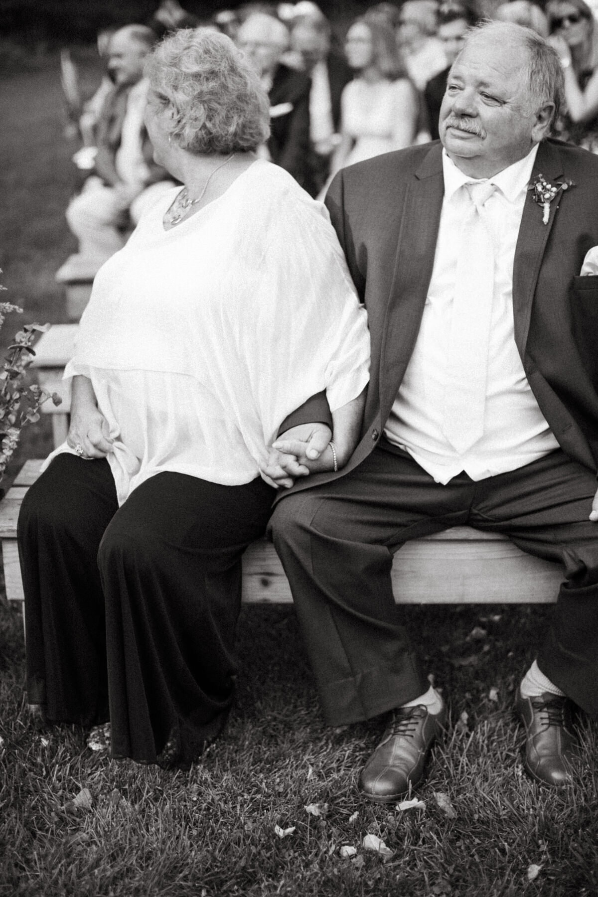 The older relatives of one of the soon to be newlyweds wait for the wedding to begin while holding hands, with the woman holding the man's hands and looking expectantly down the aisle.
