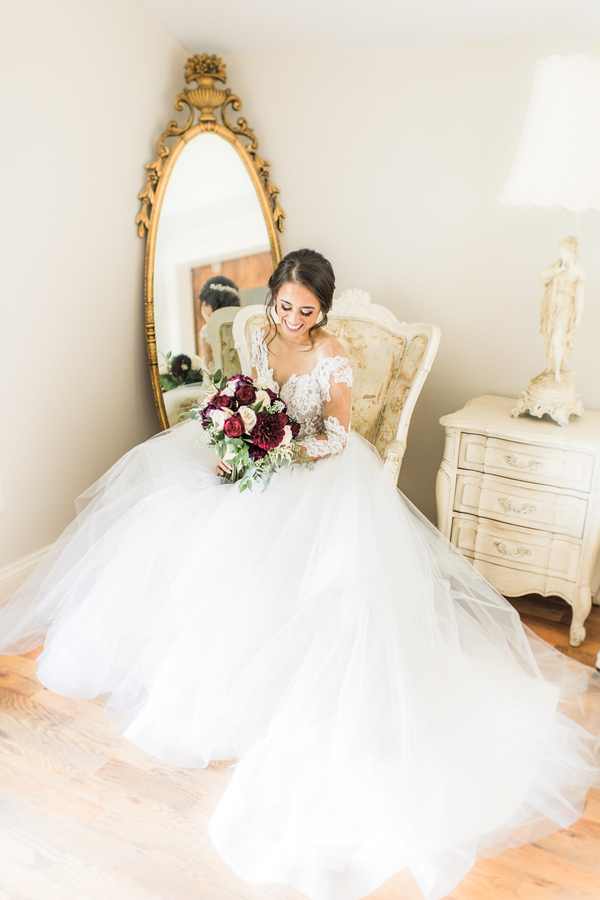 Bride in Hayley Paige wedding dress looking at her white and burgundy bouquet