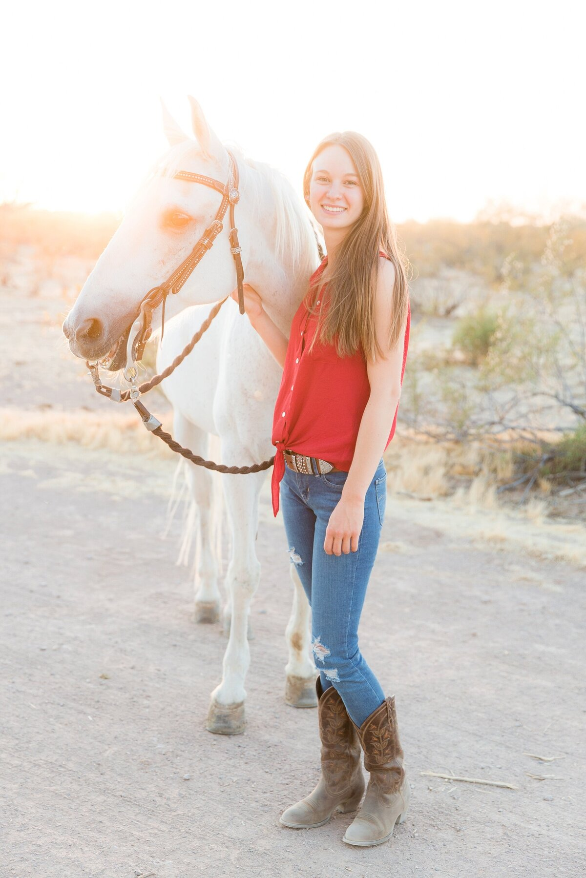 girl standing next to her grey horse in a western bridle while smiling at the camera