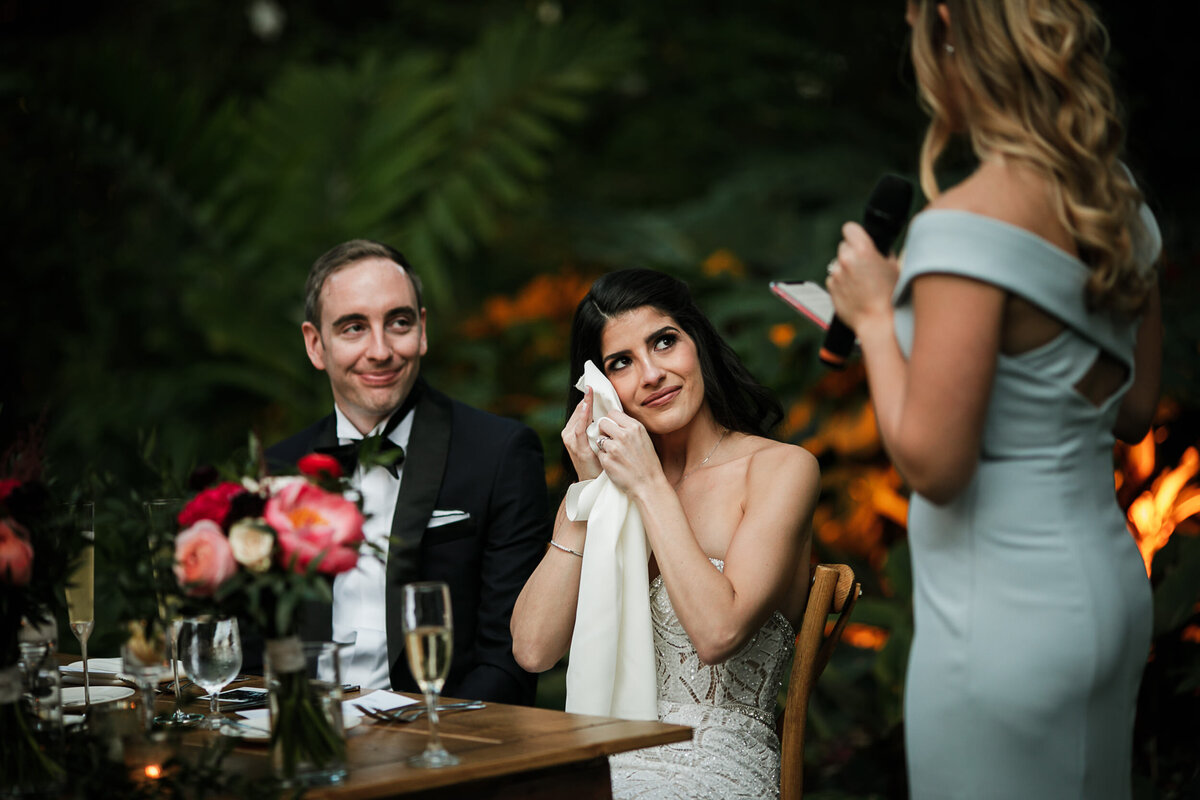 Bridesmaid gives toast to couple sitting at the sweetheart table while the bride wipes a tear away with a napkin