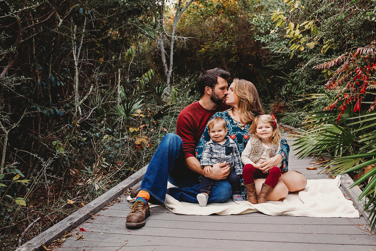 Mom and dad kiss while kids look at camera, laughing