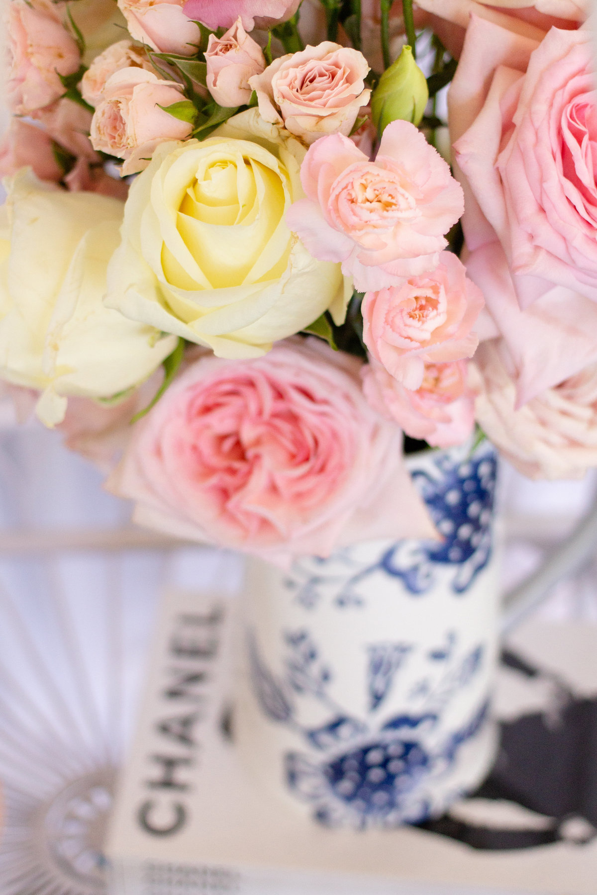 Blush wedding flowers in a luxury blue and white vase on Chanel magazine