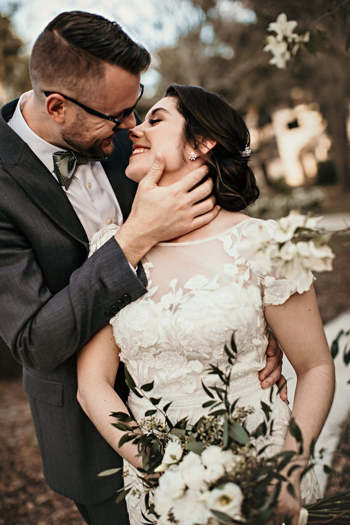 A picture of a closeup view of the bride looking up at the groom behind her as he tenderly holds her neck and leans in as they smile with their faces romantically close on their wedding day