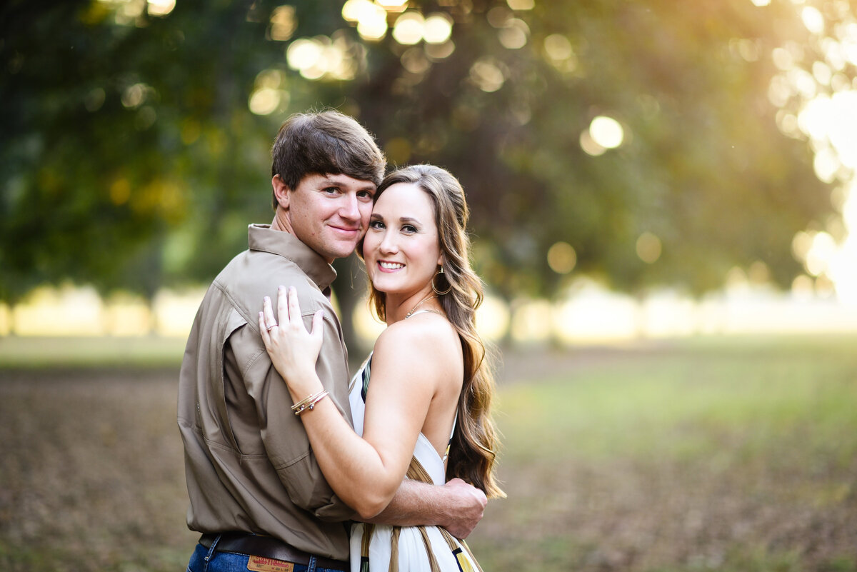 Beautiful Mississippi Engagement Photography: Couple embraces during sunset in Mississippi Delta pecan orchard