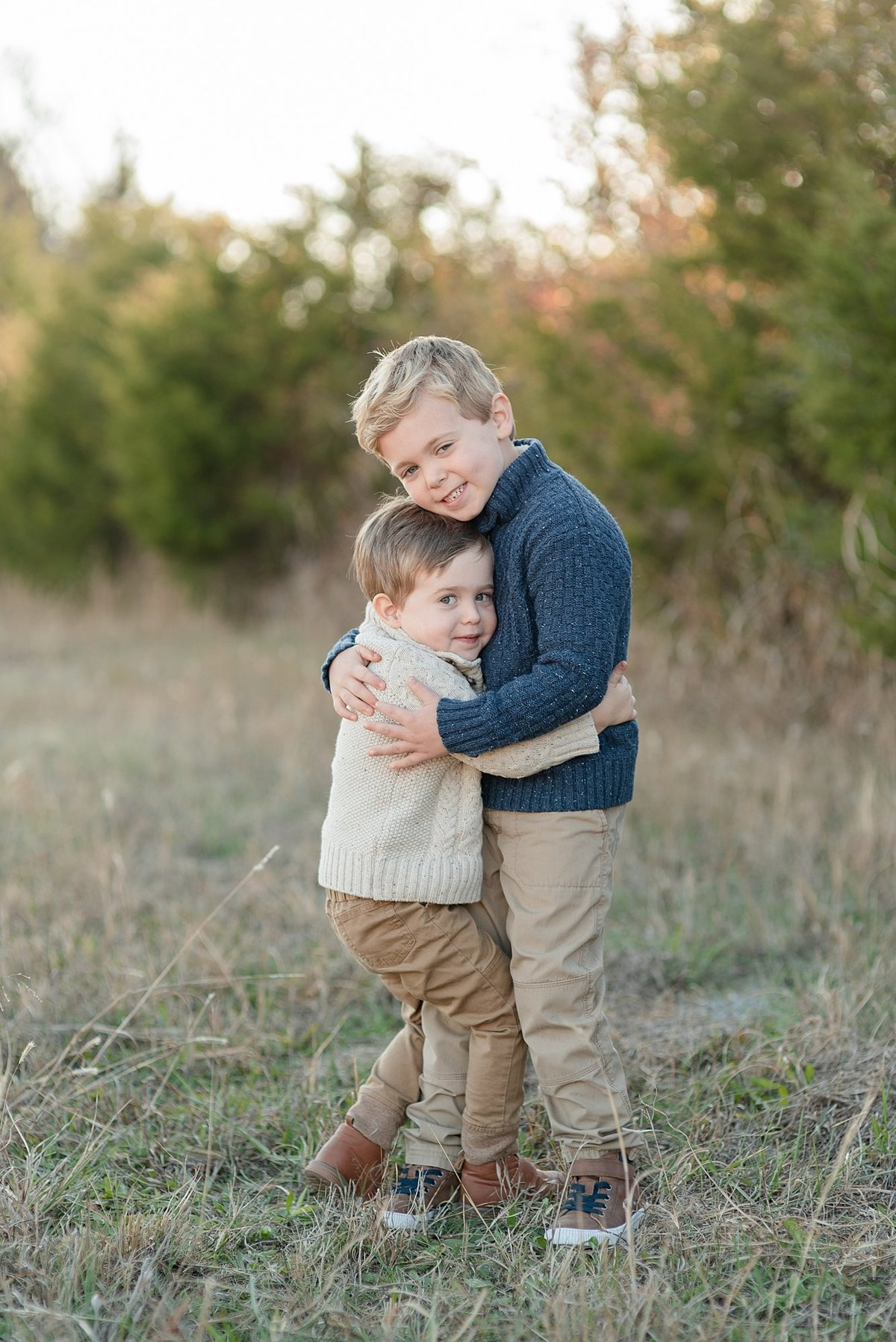 Two brothers are smiling and hugging eachother for family portraits