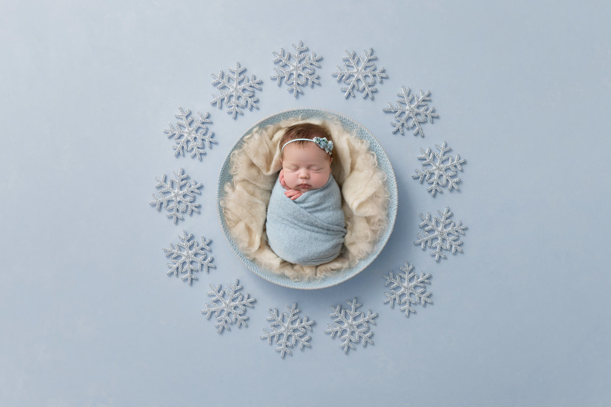 Baby girl surrounded by snowflakes in a bowl
