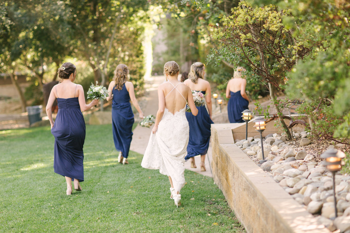Bride and bridesmaids walk in vineyard at Firestone Winery wedding