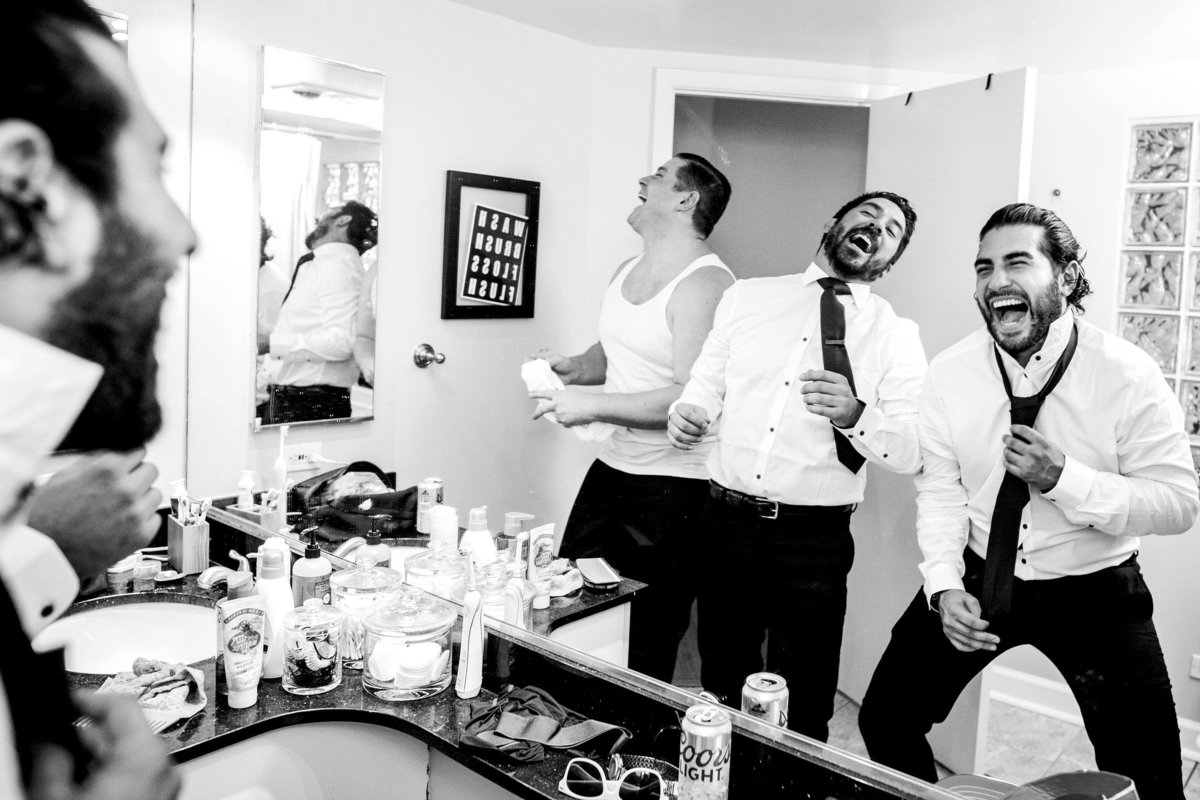 Groomsmen laugh while getting ready before an Ovation Chicago wedding.