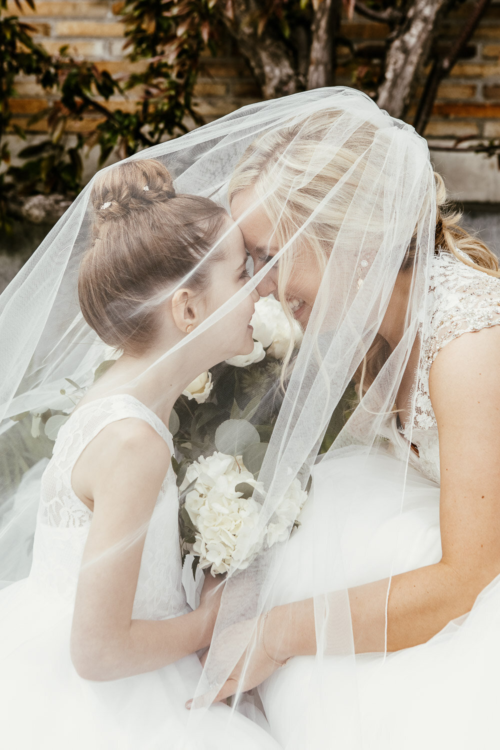 Bride and flower girl under wedding veil in Buffalo, New York