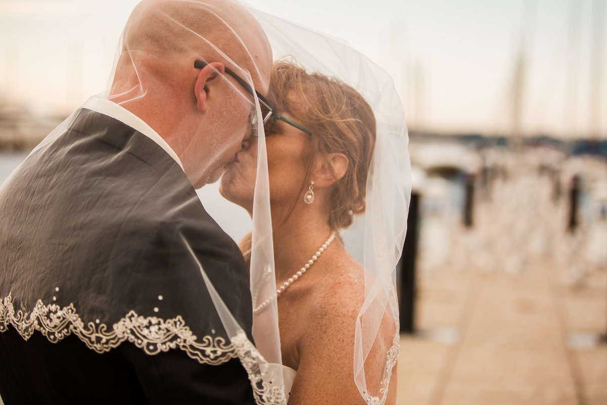 Bride and groom kiss on a dock at the Erie Yacht Club