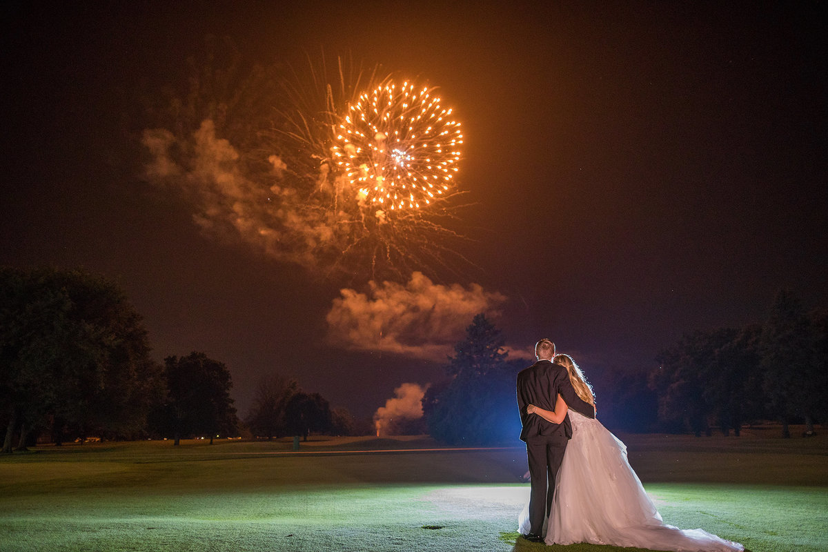 Bride and groom watching fireworks at the end of their wedding