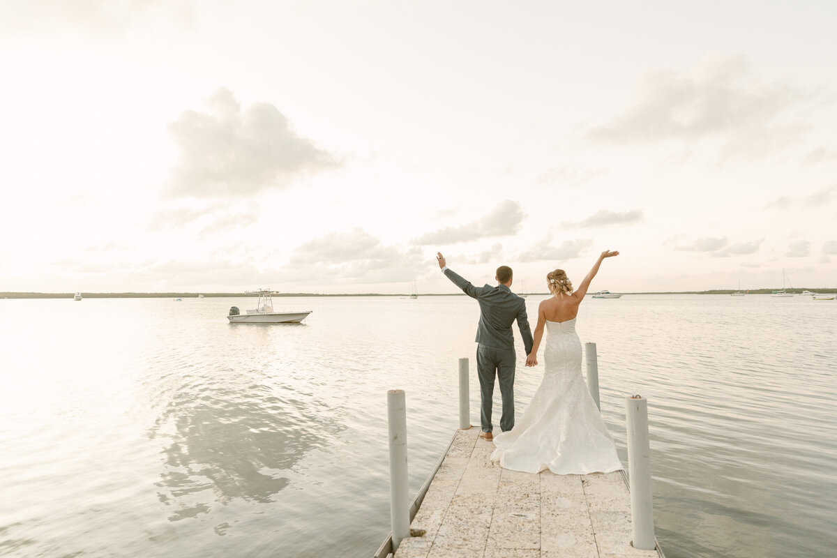 Bride and groom wave from the end of a dock
