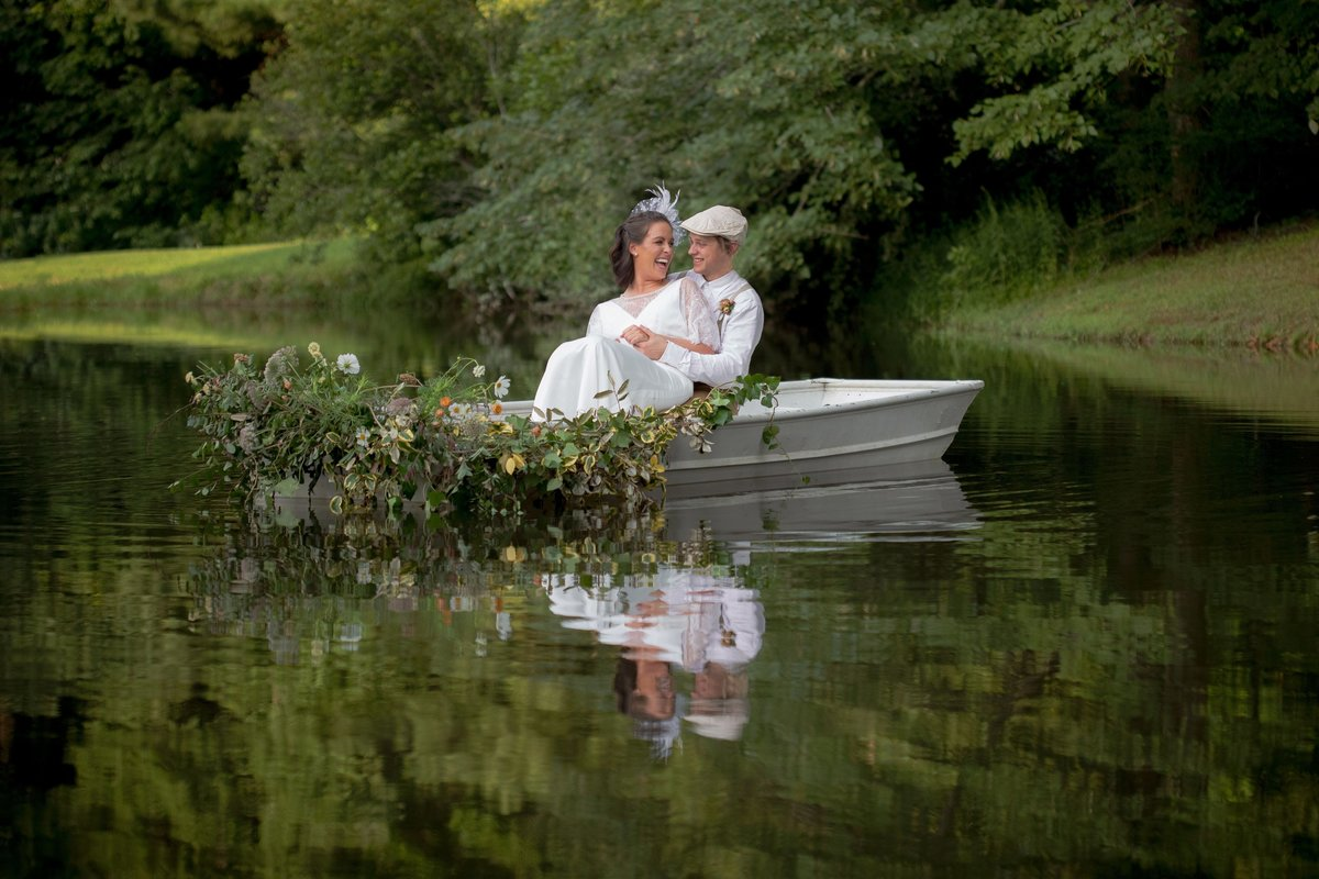 1940's styled wedding of bride and groom in john boat in lake