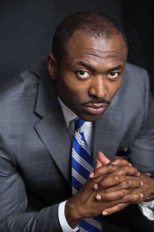 An African American black sales professional poses for a professional headshot photo on a dark grey background at Janel Lee Photography studios in Cincinnati Ohio