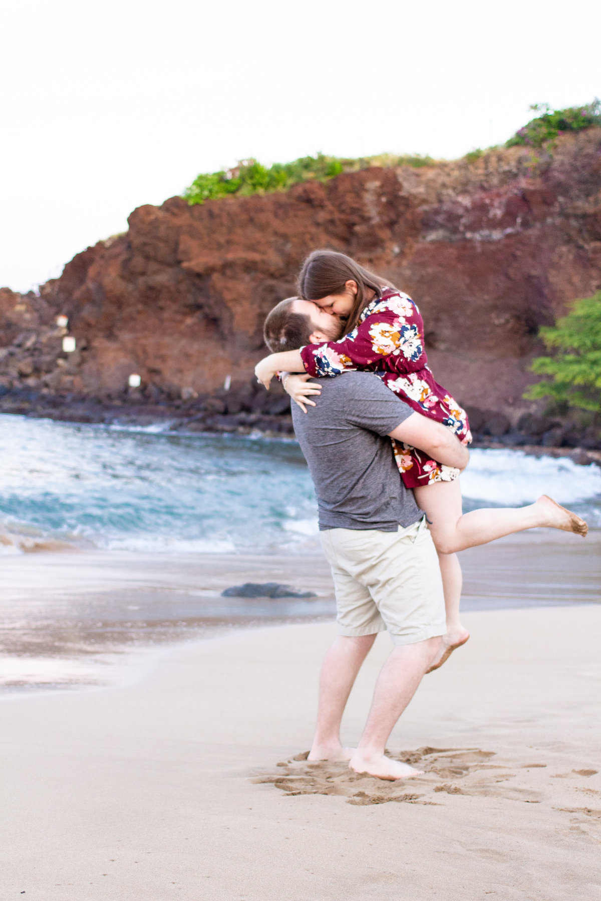 Couple does a lift kiss at the beach in Maui, Hawaii during the destination engagement photo session