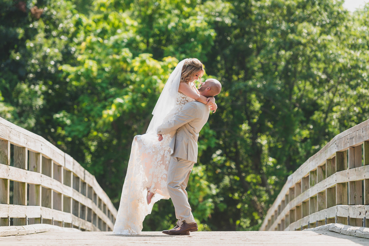 photo of groom holding up bride on bridge from wedding at Pavilion at Sunken Meadow