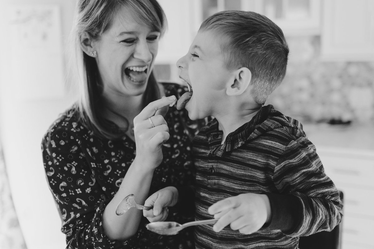 Mom and son making muffins licking batter