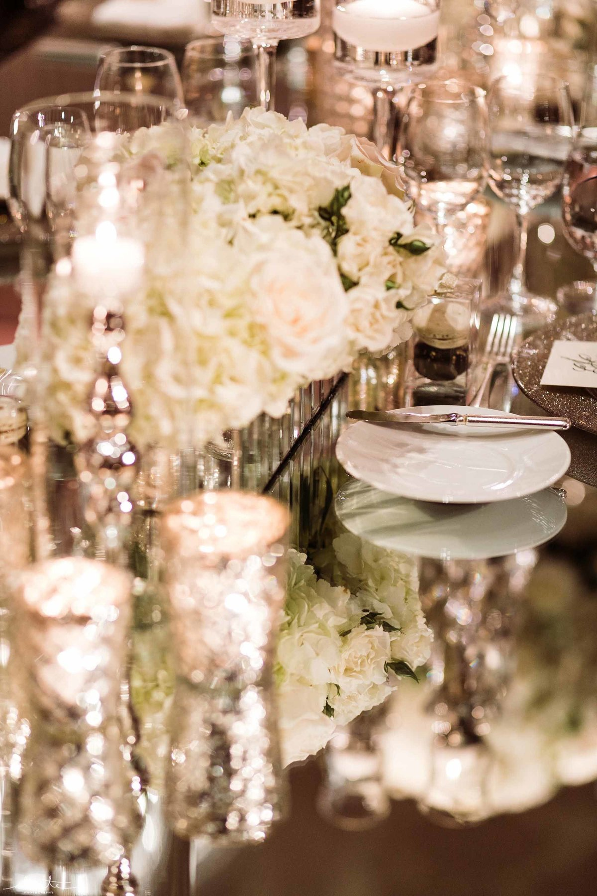Glam mirrored table filled with white flowers and candles.