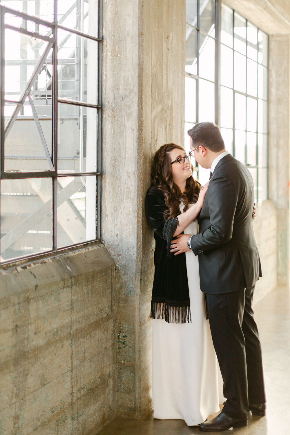 Bride and groom embracing and smiling in industrial hallway