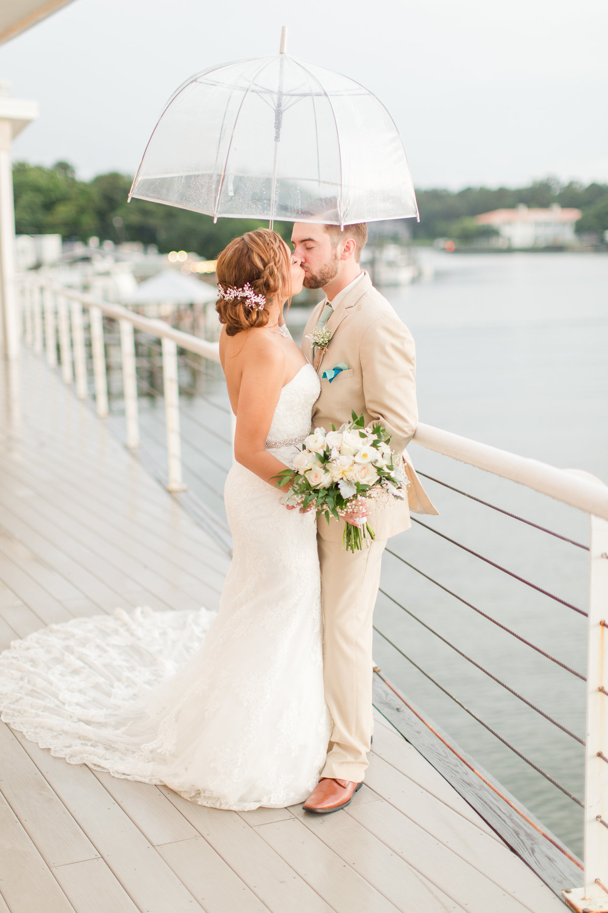 Bride and groom kissing under an umbrella a Lesner Inn