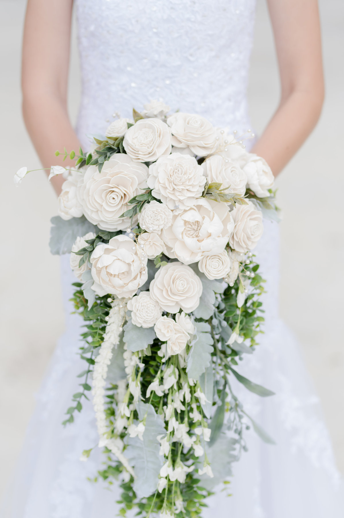 Bride holds beautiful bouquet of white roses and trailing greenery