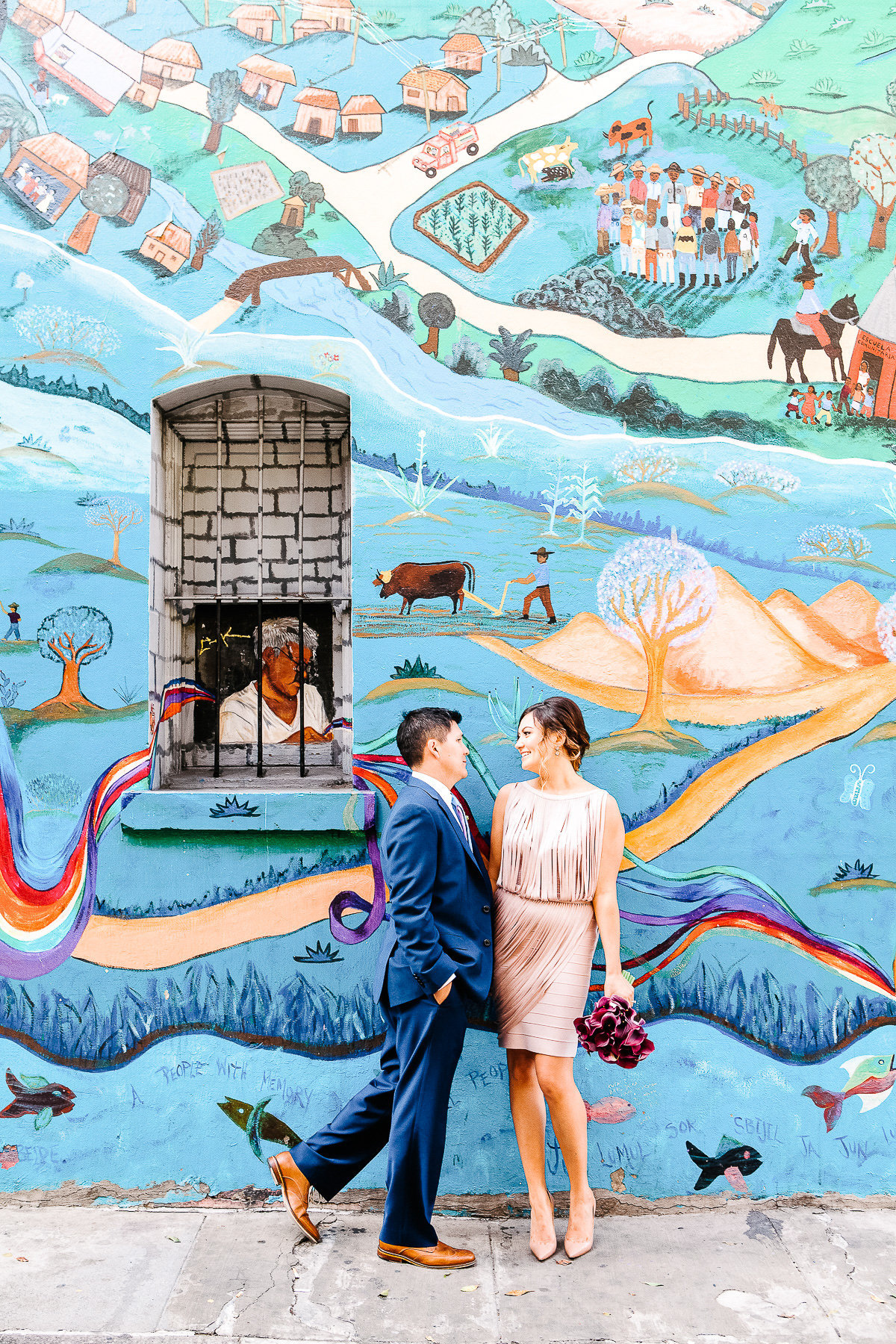 An elopement in San Francisco with a mural as a background.