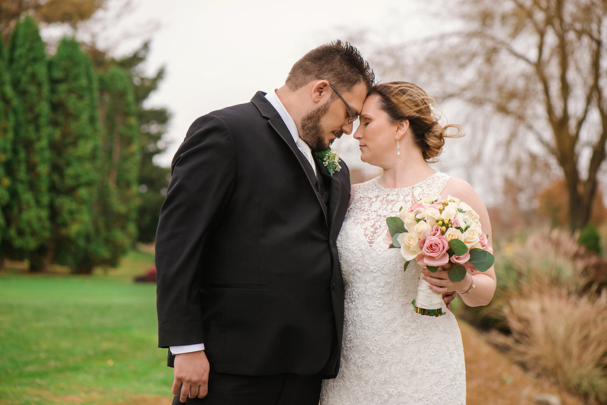 bride and groom touching foreheads on the golf course at Willow Creek Golf and Country Club
