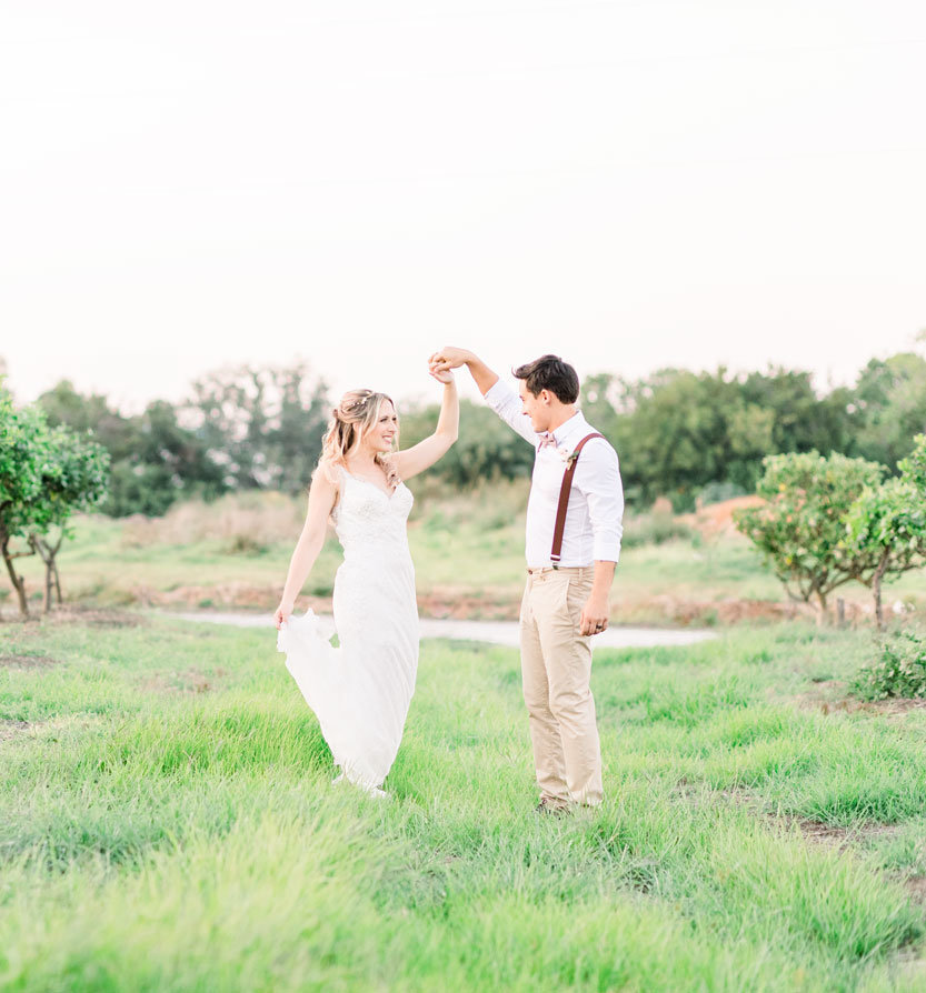 Husband and wife twirling in an orchard