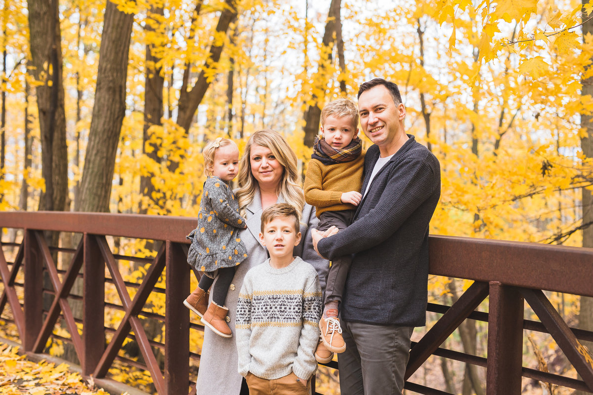 Family of 5 standing by bridge in fall foliage {Etobicoke Family Photographer}