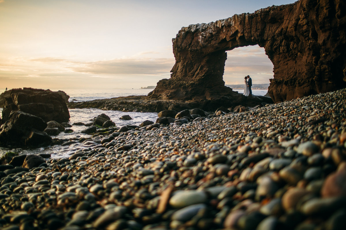 Bride & groom embrace under a natural rock arch formation before their Mexico destination wedding.