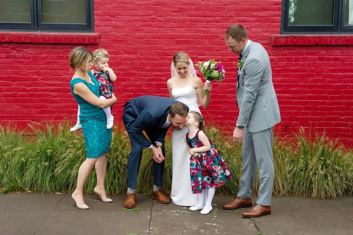 a groom leans down so a flower girl can kiss his cheek in front of a vibrant red wall