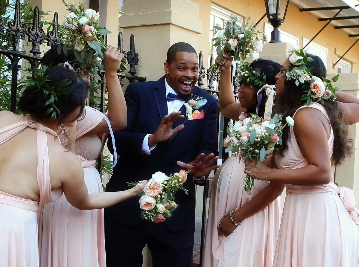 groom cutting up with bridesmaids