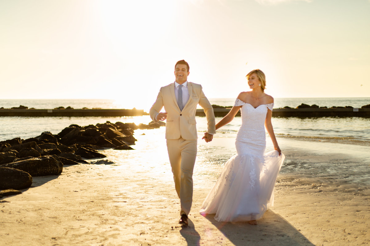 Bride holds the trail of her mermaid wedding dress as she runs on the beach at sunset holding hands with her groom in his tan suit in Dunedin, Florida