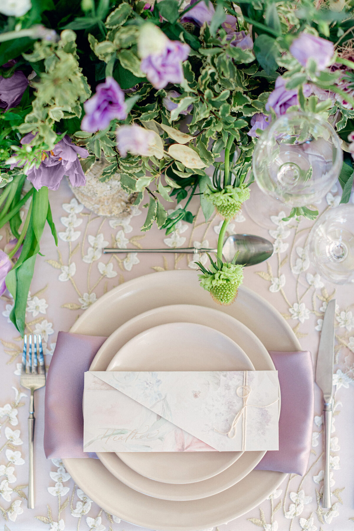 Reception table plate with purple florals in patio room at Lowndes Grove Charleston Wedding