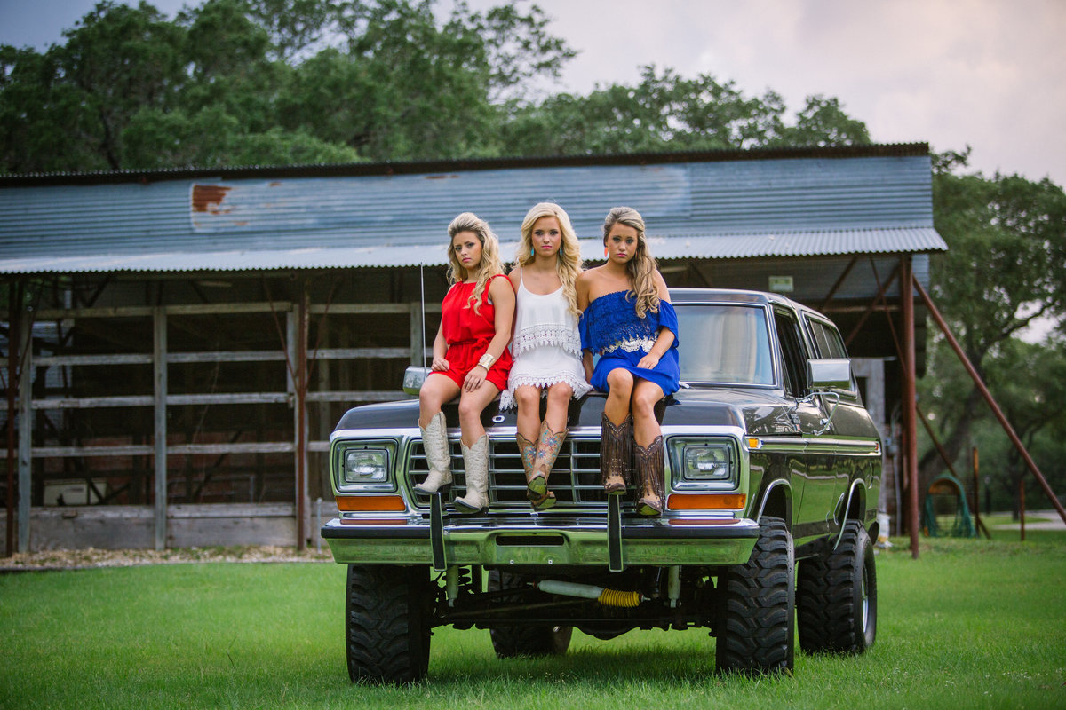 high school senior session of three girls sitting on truck by San Antonio senior photographer