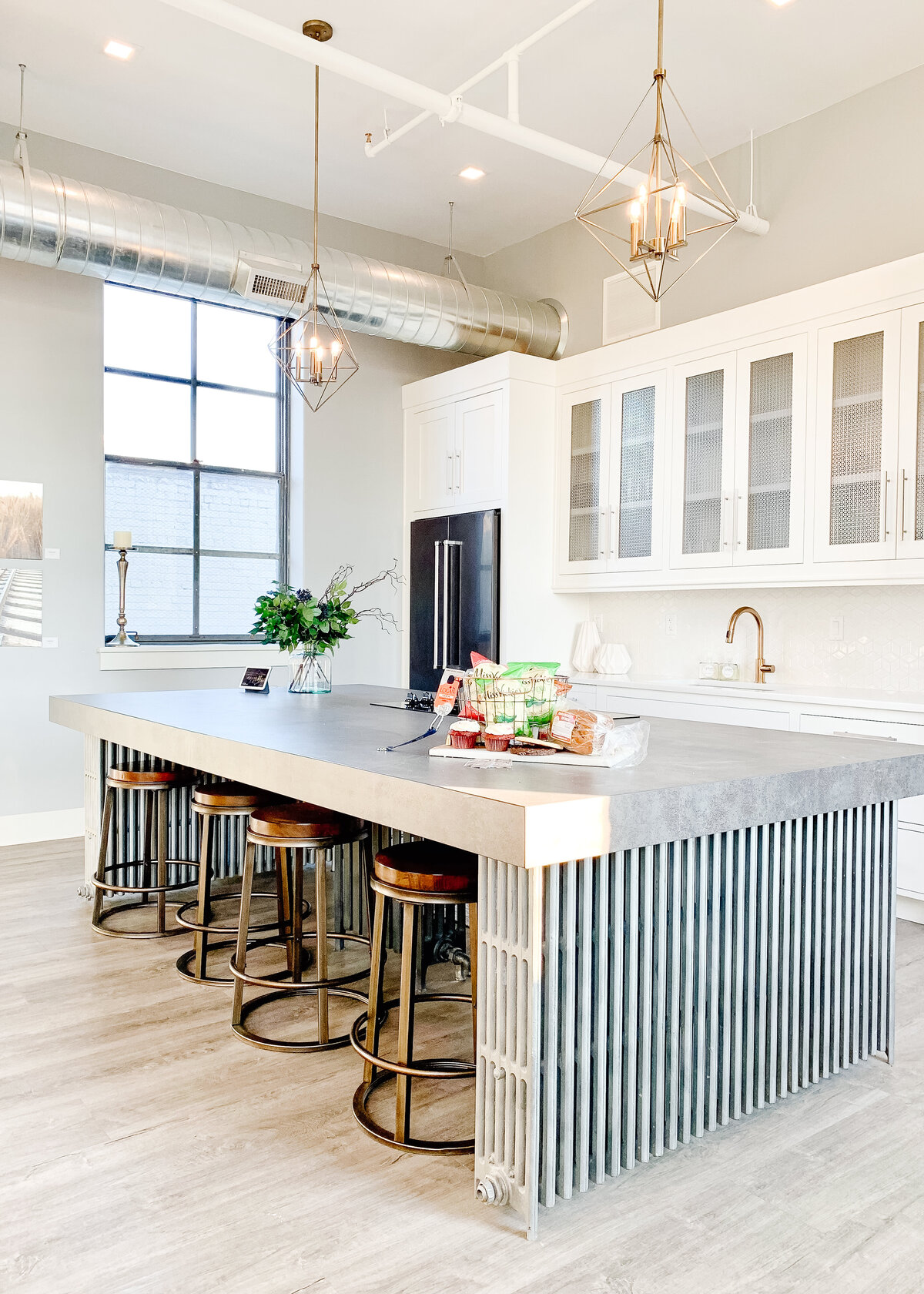 A white, industrial kitchen with a large central island made with old radiators below geometric pendant lights.