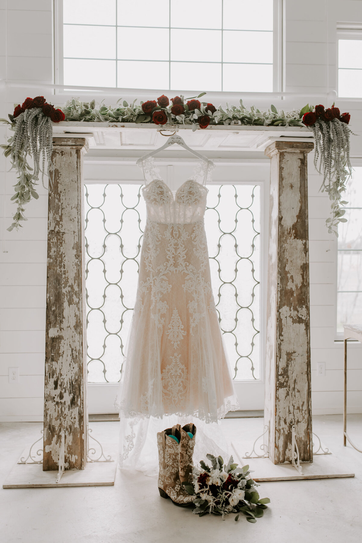 A lace wedding dress hanging in the chapel. There are wedding cowgirl boots in front of the dress with the brides bouquet