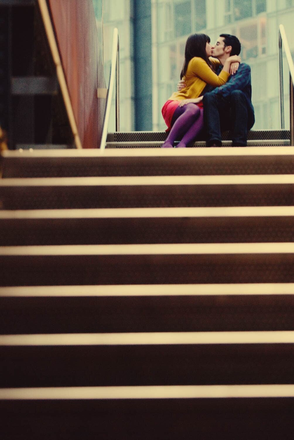 a colorful couple sit at the top of stairs and kiss in nyc