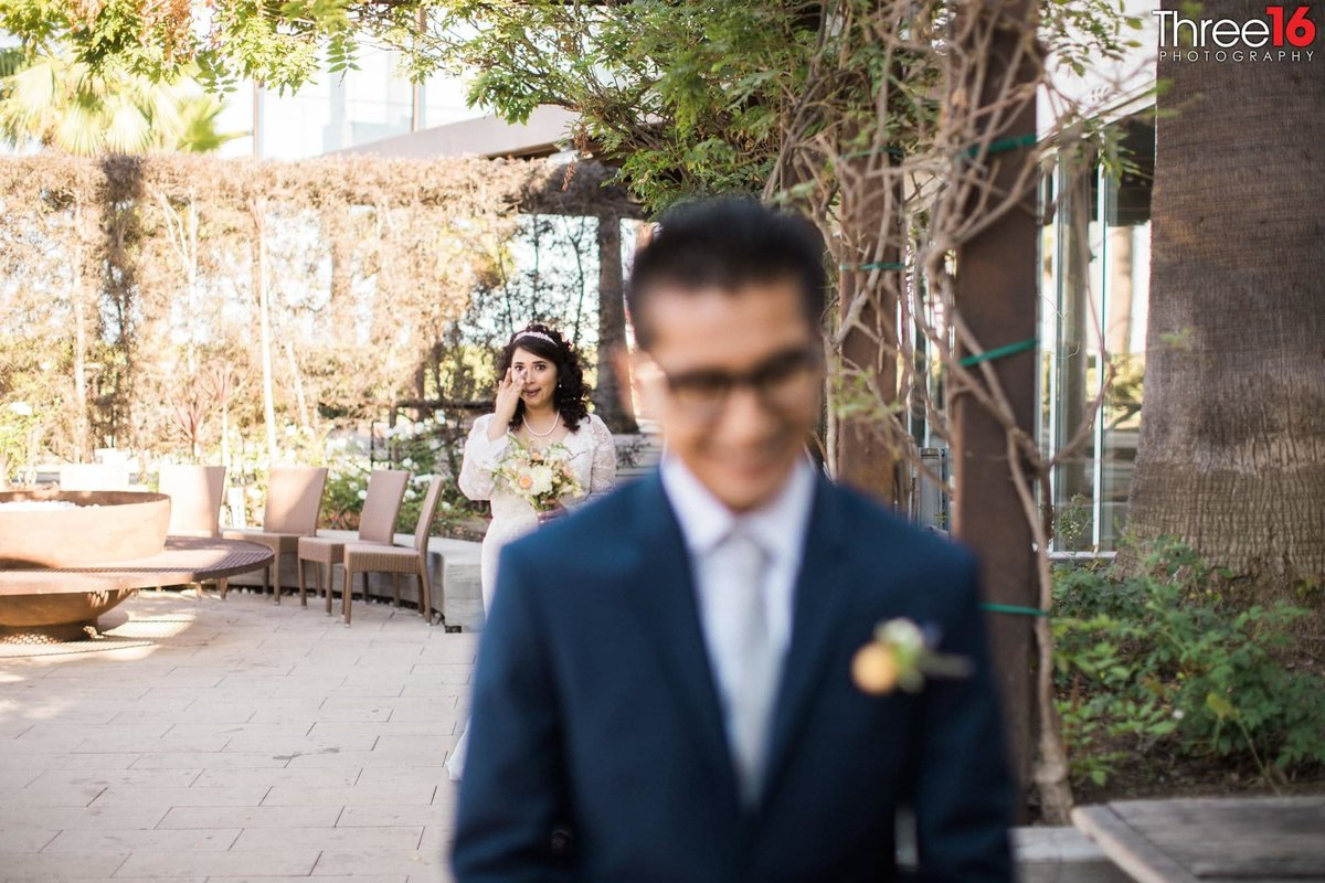Groom waiting as Bride approaches for the First Look