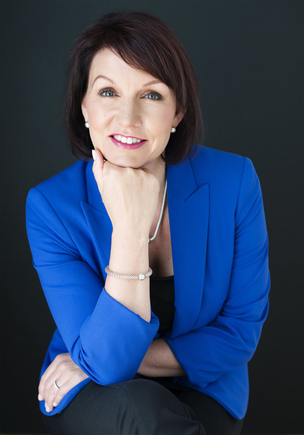 confident headshot of  business woman sitting on chair with hand  under chin wearing blue jacket looking into camera  photograph taken by oakville best photography studio