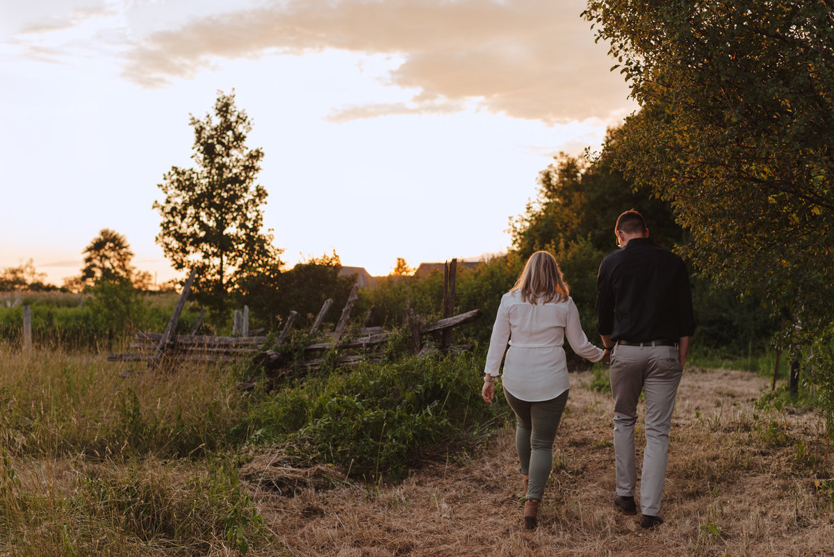 engaged couple holding hands walking through a field at sunset
