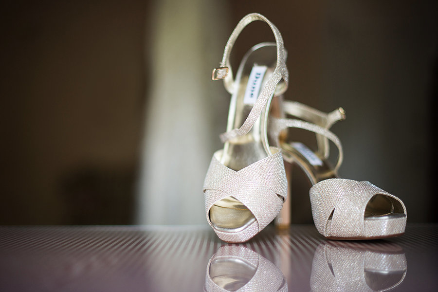 Bridal shoes reflect on a glass table in Bellevue Mansion in Delaware