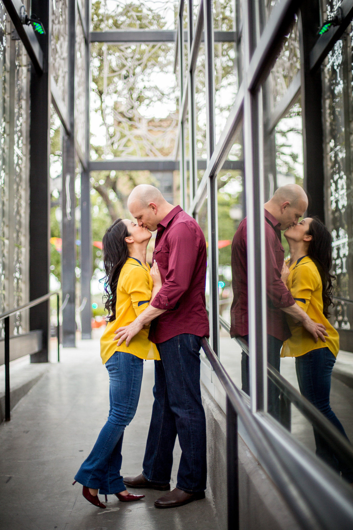 Engaged couple embracing and kissing and you can see their reflection on the building next to them.